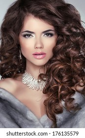 Beauty portrait. Wavy hair. Beautiful brunette woman with long curly hair. Makeup. Hairstyle. Jewelry. Winter girl.