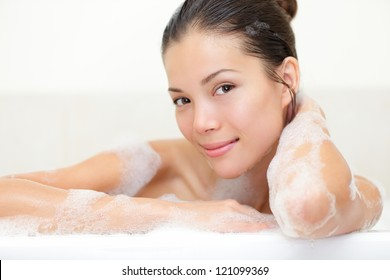 Beauty portrait of woman in bathtub with bath foam smiling happy looking serene at camera. Beautiful young mixed race Caucasian / Asian woman.