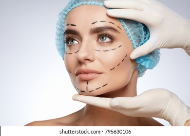 Beauty portrait of woman in blue cap looking aside, plastic surgery concept, studio. Hands in white gloves holding face of model with puncture lines, indoors