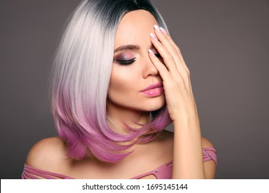 Beauty Portrait of woman with bob short hairstyle. Beautiful coloring  hair. Trendy purple haircut. Blond model with short shiny haircuts isolated on grey Background. Makeup. Manicured nails.