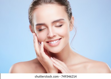 Beauty portrait of woman with closed eyes touching face with slight smile. Head and shoulders of tender woman with nude make-up, beauty concept. Indoors, studio