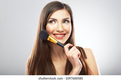 Beauty portrait of woman holding make up brush. Isolated close up face portrait of smiling girl.