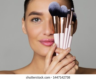 Beauty Portrait of Woman with Makeup Brushes near Face, Grey Background, Crop