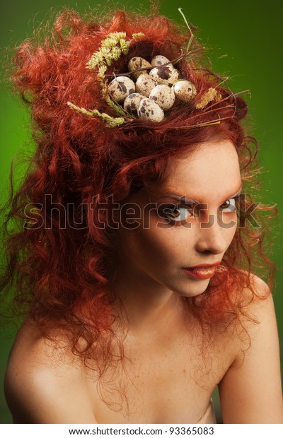 Beauty portrait of woman with nest in curly red hair