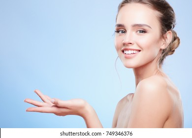 Beauty portrait of woman with stretched hand, semi profile. Head and shoulders of woman with nude make-up looking at camera and smiling, beauty concept, turned aside