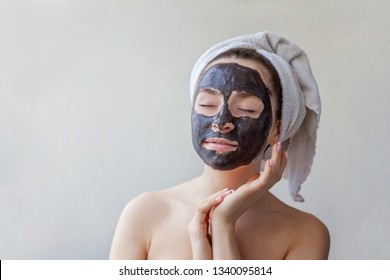 Beauty portrait of woman in towel on head applying black nourishing mask on face, white background isolated. Skincare cleansing eco organic cosmetic spa relax concept