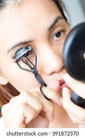 Beauty portrait of woman using eyelash curler