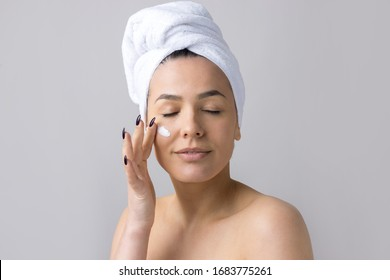 Beauty portrait of woman in white towel on head applies cream to the face. Skincare cleansing eco organic cosmetic spa relax concept.