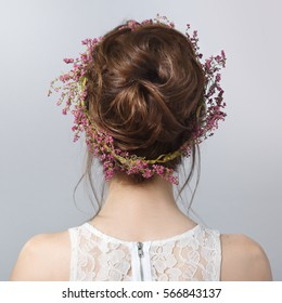 Beauty portrait with wreath of heather in the hairstyle from the back isolated on a gray background.