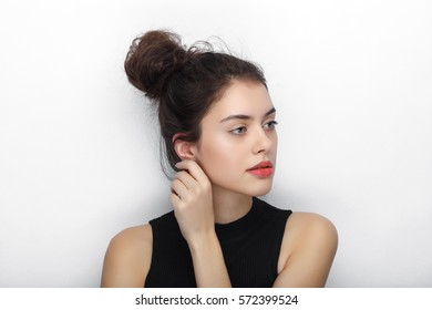 Beauty portrait of young adorable fresh looking brunette woman with high bun hairdo touching her ear. Emotion and facial expression concept.