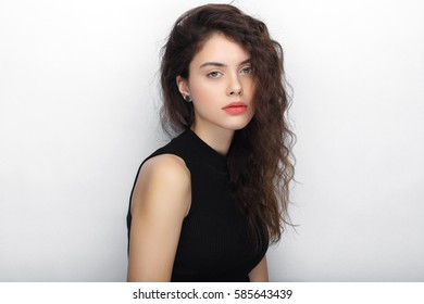 Beauty portrait of young adorable fresh looking brunette woman with long brown healthy curly hair. Emotion and facial expression concept.