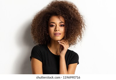 Beauty portrait of young adult african american woman with afro hairstyle looking at camera isolated on white background