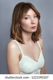 Beauty portrait of young adult woman dressed white lace top.