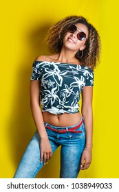Beauty portrait of young african american girl with afro hairstyle in sunglasses. Girl posing on yellow background, looking at camera. Studio shot.