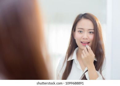 Beauty of portrait of young asian woman at the mirror holding and looking a makeup lipstick, Beautiful girl beauty fashion at the room, lifestyle concept.