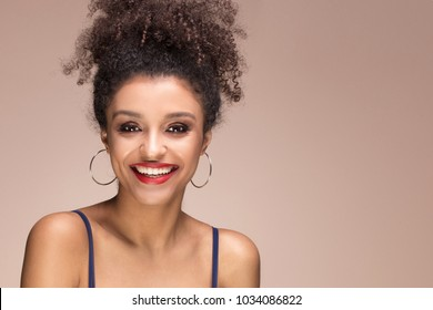 Beauty portrait of young attractive african american woman with amazing toothy smile and glamour makeup.