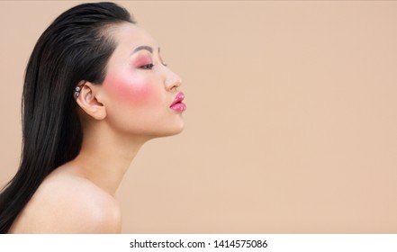 Beauty portrait of young attractive asian woman with bright make up over beige background