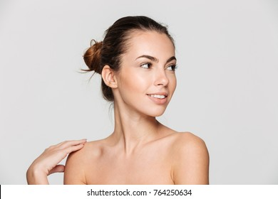 Beauty portrait of a young attractive half naked woman with perfect skin looking away isolated over white background