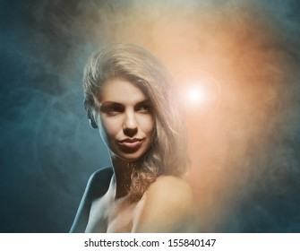Beauty portrait of young attractive woman over smoky background
