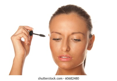 Beauty portrait of a young and attractive woman applying mascara isolated on white background