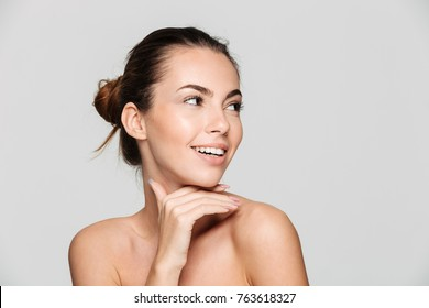 Beauty portrait of a young beautiful half naked woman with perfect skin looking away isolated over white background
