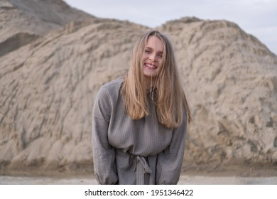 Beauty portrait of a young blond girl in a vintage dress. She is posing on a sandy landscape.