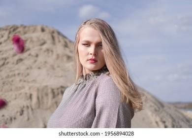 Schönes Porträt eines jungen blonden Mädchens in einem Vintage-Kleid. Sie posiert auf einer sandigen Landschaft.