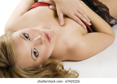 beauty portrait of young blond woman in black underwear with hair style laying down on white