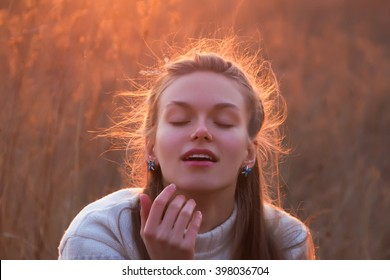Beauty portrait of a young blonde woman at sunset. Girl's hair backlit by the yellow hot sunlight. She closed her eyes and slightly opened lips. She enjoys and gets pleasure. Girl daydreams.