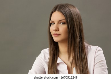 Beauty portrait of young brunette in classic white shirt. Studio shot of young beautiful woman.