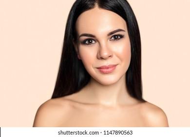 Beauty portrait of young brunette woman with perfect healthy  skin and smooth hait. Attractive model with natural professional make up. Hairdress salon and cosmetics concept