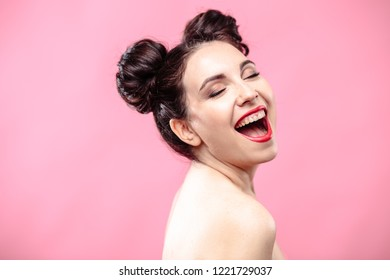 Beauty portrait of young brunette woman on a bright pink background. Model with make-up and hairstyle, closeup, fashion glamour photo