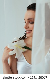 Beauty portrait of young brunette woman with beautiful make up, tan sking holding lily flower while posing on white background. Skincare cosmetics, Wellness