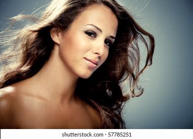beauty portrait of young brunette woman, hair fly, studio shot