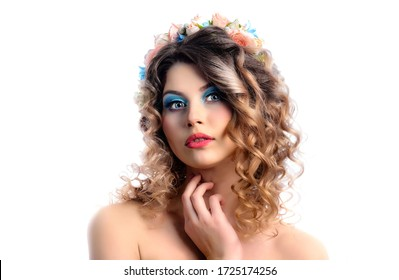 Beauty portrait of a young cute model with bright makeup and flowers in her hair. Close-up portrait