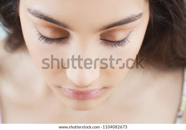 Beauty portrait of young ethnic woman with flawless skin wearing natural make up cosmetics, looking down with eyes shut, perfect eye lashes and brows. Healthy female face, feminine purity, lifestyle.