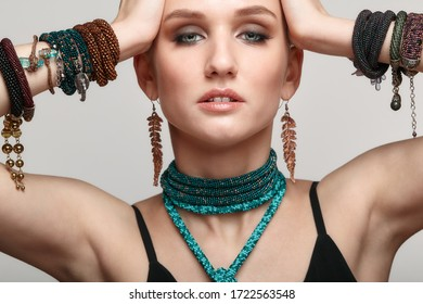 Beauty portrait of young female with hands up on gray background. Beautiful woman in collar necklace and multiple bracelets on hands.