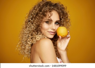 Beauty portrait of young girl with afro hairstyle. Girl posing on yellow background with orange. Healthy eating concept. Studio shot
