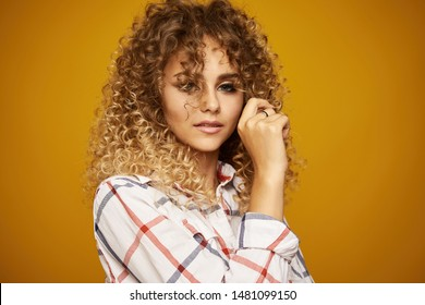 Beauty portrait of young girl with afro hairstyle. Girl posing on yellow background. Studio shot