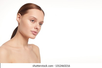 Beauty portrait of young girl with brown hair and big lips on white background with clean face skin and arm near head. Good for cosmetic, medicine and spa . European type