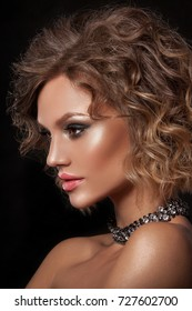 Beauty portrait of a young girl with clean skin of the face. Wavy hair, photographed on a black background. Ã?lose-up