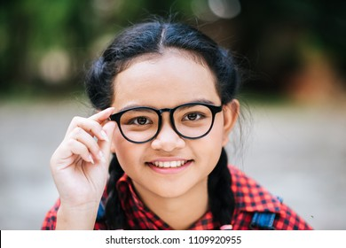 Beauty portrait of a young girl holding glasses and looking at camera