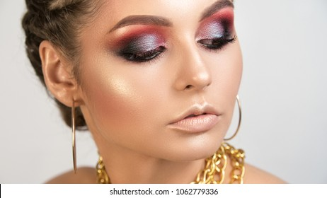 Beauty portrait of young girl with the shining smooth healthy skin of person bright expressive smoke-coloured make-up and gold on lips