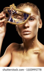 Beauty portrait of young gorgeous woman. Female with masquerade venecian mask in hand near face. Golden girl on black background