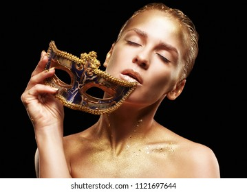 Beauty portrait of young gorgeous woman. Female with masquerade venecian mask in hand near face and eyes closed. Golden girl on black background