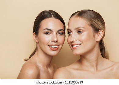 Beauty portrait of young happy optimistic cheery beautiful blonde and brunette women posing naked isolated over beige wall background.