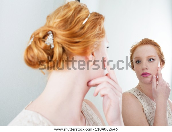 Beauty portrait of young red hair bride woman with romantic hair do looking at herself in the mirror, indoors. Healthy female reflection, skin care, wedding preparation. Cosmetics lifestyle.