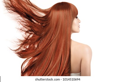 Beauty portrait of a young redhead woman with dyed healthy shiny long hair in a copper color with highlights flying away to the side in the wind isolated on white viewed from the rear