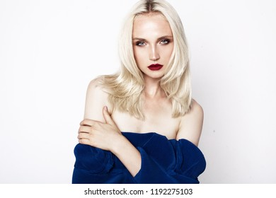 beauty portrait of young woman with blonde hair and bright makeup. Red lips. White background