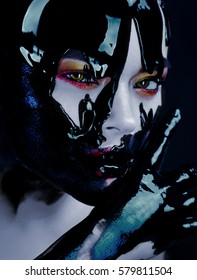 Beauty portrait of a young woman with bright makeup on the face which runs black paint covering the skin. Black oil, lacquer, paint.